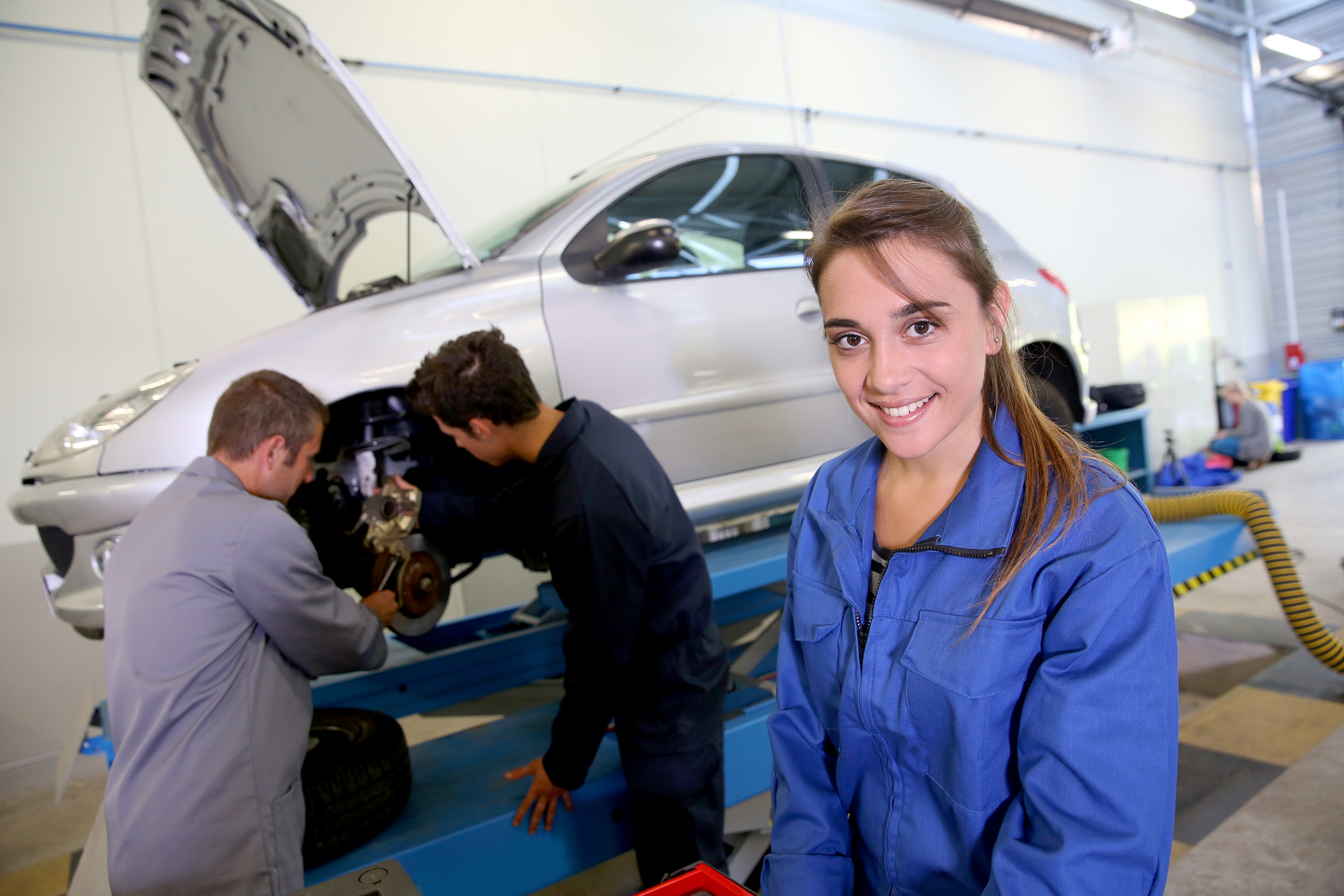 Teacher and students at work in garage